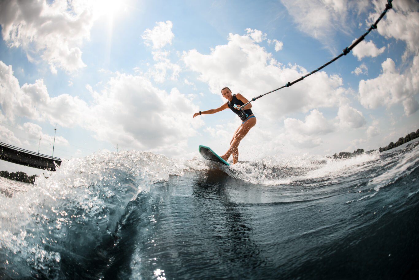 Young,beautiful,woman,riding,on,the,wake,surf,holding,rope